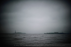 Liberty and Ellis Islands during a foggy rainy day in New York City. Taken wide open at f/1.2. Contrast and levels adjust to emphasize the vignetting at this wide open aperture.